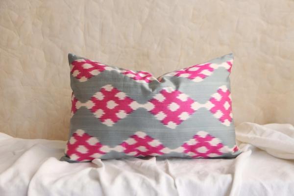 Almohadon en tonos gris, blanco y rosa.