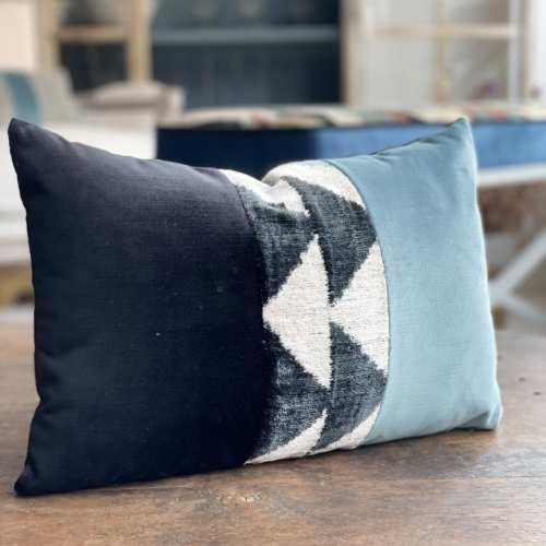 Almohadón con motivos geométricos en tonos azul, negro y gris