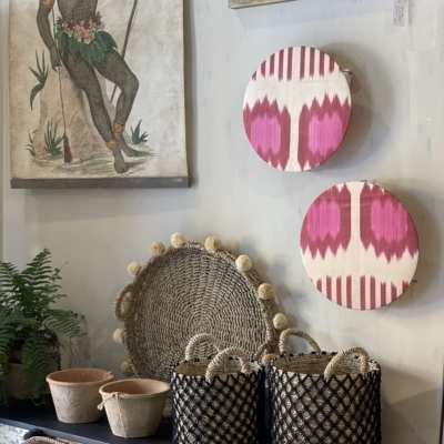 Lámpara de pared circular realizada en ikat de seda con tonos beige y frambuesa .
