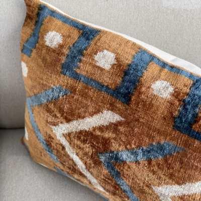 Almohadón realizado en ikat de terciopelo en tonos tierra , azul y blanco roto.